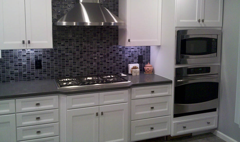 European kitchen cabinetry with stainless hood vent