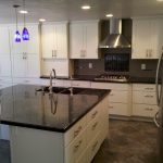 White kitchen cabinets with stainless hood and sink in island